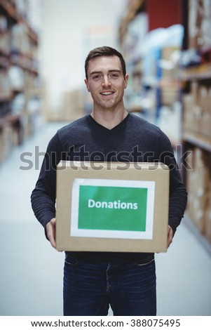 Volunteer smiling at camera holding donations box in warehouse - stock photo