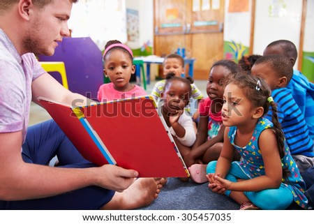 Volunteer teacher reading to a class of preschool kids - stock photo