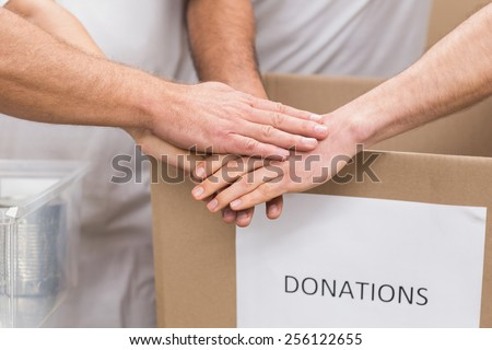 Volunteer team holding hands on a box of donations in a large warehouse - stock photo