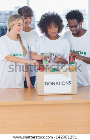 Volunteers putting food in donation box in their office - stock photo