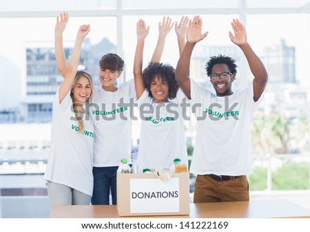 Volunteers raising their arms in front of food in a donation box