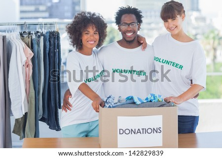 Volunteers standing together in their office in front of donations box