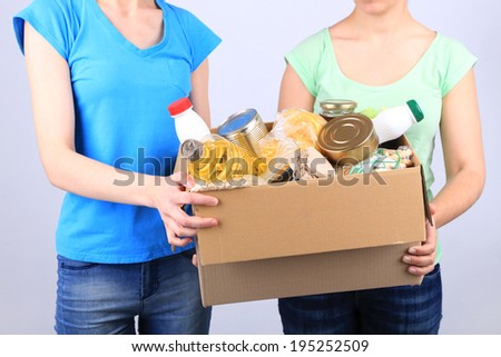 Volunteers with donation box with foodstuffs on grey background - stock photo