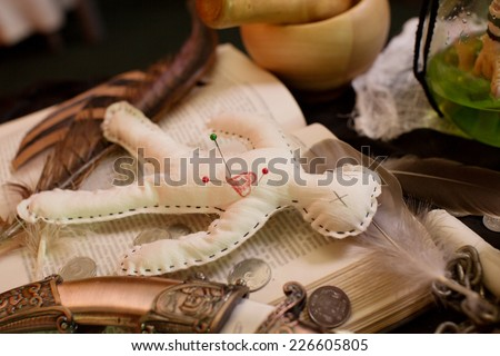 Voodoo gypsy putting needles in a doll casting a spell or curse. Halloween background - stock photo