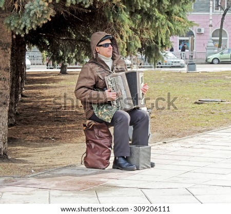 VORONEZH, RUSSIA - April 4, 2015: Mature men sitting on the camp stool in the street and playing the accordion on April 4, 2015 in Voronezh, Russia - stock photo