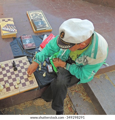VORONEZH, RUSSIA - June 12, 2015: Mature men chess player with a cigarette in his mouth makes a move on the chess board