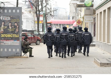 "VORONEZH, RUSSIA - MARCH 1: Group of unidentified Russian policemen pass by a disabled beggar to the rally on March 1, 2015, Voronezh, Russia. Caption on the banner (L) means ""Egoists""."