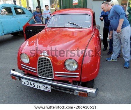 Voronezh, Russia - May 9, 2015: City dwellers look round sweden retro car of 1950s front-wheel drive coupe Saab 93 on the street near city central square during the celebration of the Victory V-E Day - stock photo