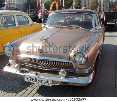 VORONEZH, RUSSIA - Sep.19, 2015: Soviet executive car of 1960s sedan GAZ M21 Volga the Third Series (Baleen) brown color with leaping deer hood ornament. Vintage car parade on the city central square  - stock photo