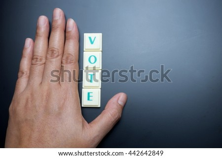 Vote concept. The words spelled by letters with hand on blackboard background. - stock photo