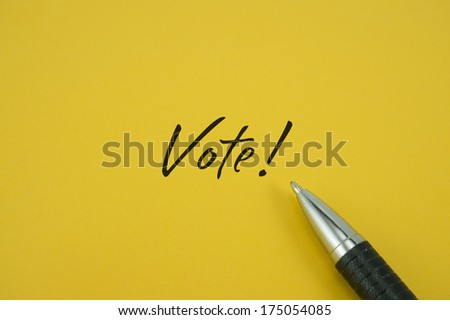 Vote! note with pen on yellow background - stock photo