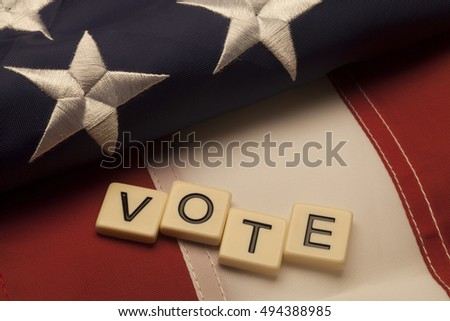 Vote scrabble letters on American flag. Concept of American election vote.