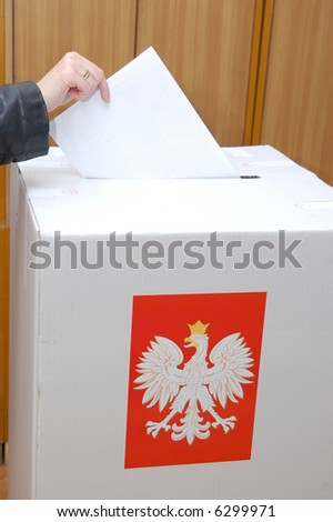 Voter casting vote into ballot box in Parliamentary election in Poland - stock photo