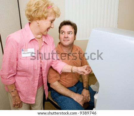 Voter receiving instructions on using a new machine from a volunteer. - stock photo