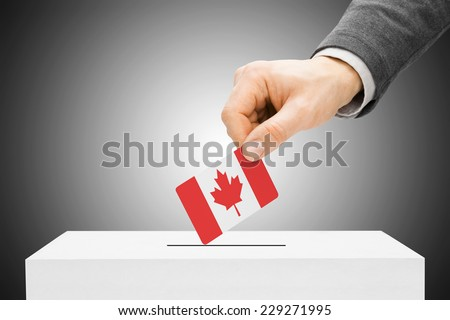 Voting concept - Male inserting flag into ballot box - Canada - stock photo