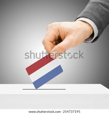 Voting concept - Male inserting flag into ballot box - Netherlands - stock photo