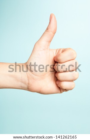 Voting hand on blue background. One hand making thumb up gesture. - stock photo
