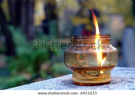 Votive candle lit on old tombstone - stock photo