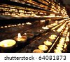 Votive church candles in rows - stock photo
