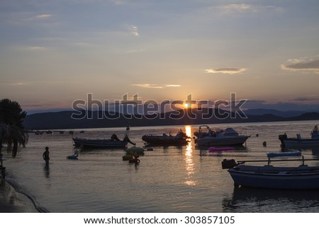 Vourvourou, Greece - June 27 2015: Boats at sea against the sunset on the shore of the beach in Vorvuru. The resort is located in Southern Europe, Halkidiki, Sithonia peninsula, the Adriatic Sea - stock photo