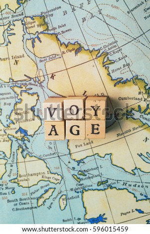 Voyage word made from wooden letter blocks on a vintage map. Travel, holiday concept