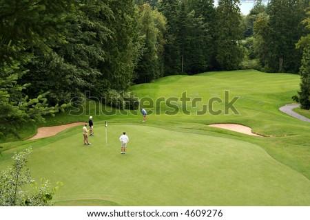 Vue de l'oeil de l'oiseau des golfeurs sur un beau vert demise. - stock photo