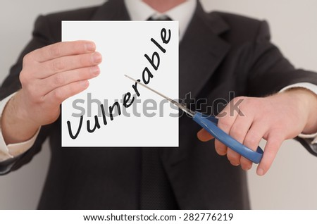 Vulnerable, man in suit cutting text on paper with scissors