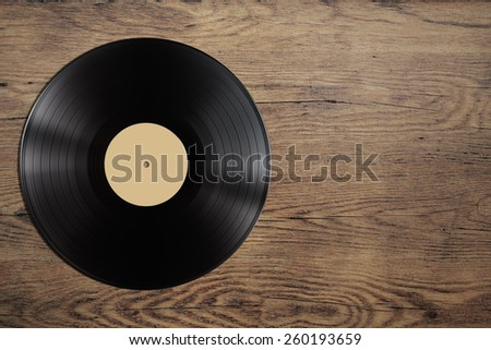 vynil record disc on wooden table - stock photo