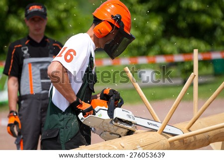 VYSHGOROD, UKRAINE -  MAY 18,2013 : Man with chainsaw Stihl a protective mask cutting the tree in Vyshgorod ,Ukraine.  - stock photo