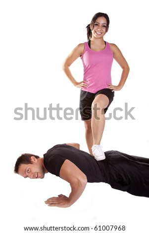W couple is working out.  The man doing pushups, and the woman stepping on his back - stock photo