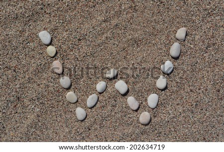 W letter made of stones on sand  - stock photo