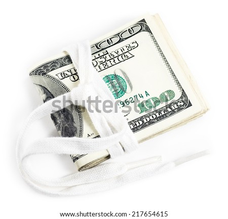 Wad of cash and shoestring implying a tight budget concept image.  - stock photo
