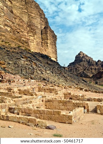 Wadi Rum desert hills with ruins of nabatean temple in Jordan - stock photo