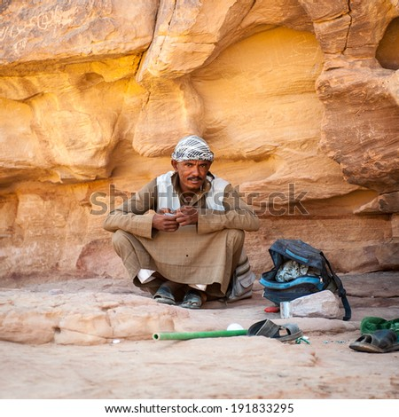 WADI RUM, JORDAN - APR 30, 2014: Unidentified bedouin near the rock in the desert of Wadi Rum. Bedouins are a part of a desert-dwelling Arabian ethnic group
