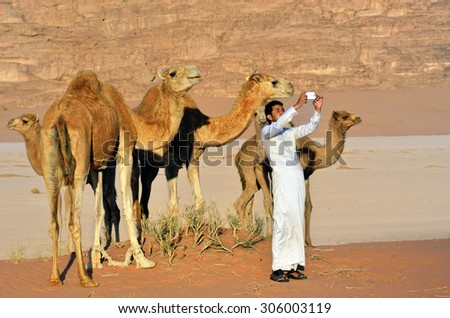 WADI RUM, JORDAN - APR 2, 2015: Unidentified jordanian man makes selfie with a camels in Wadi Rum desert at sunset. Selfie is a craze, which gripped the whole World