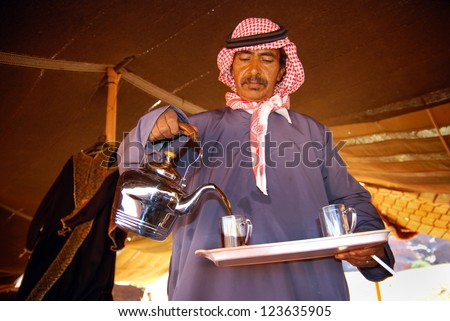 WADI RUM - NOV 10:Jordanian Arab Bedouin man pouring hot tea from a tea jug in Wadi Rum, Jordan on November 10 2007.The Bedouins are world famous for their culture and warm hospitality in the desert. - stock photo