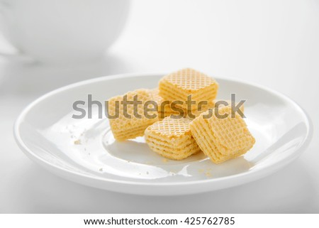 Wafer biscuits on saucer on white background - stock photo