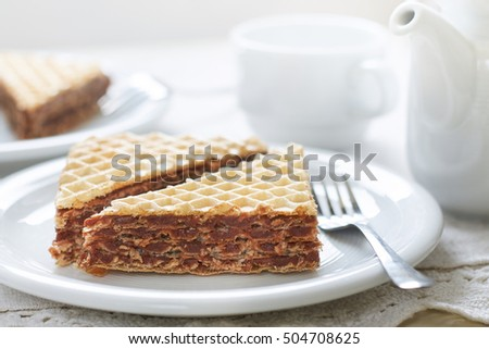 Wafer sheets filled with caramelized sugar and hazelnut cream served on white plate