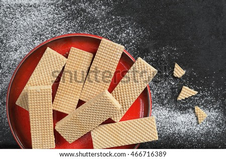 Wafers in red plate on black metal background, top view