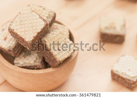 Wafers with chocolate in cup on wooden background. - stock photo