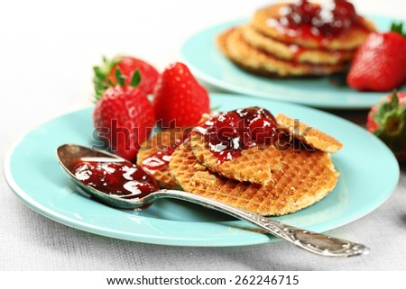 Wafers with strawberry jam and berries on plates on table close up - stock photo