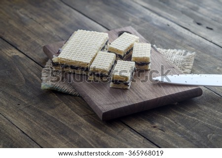 Waffle cake with  chocolate on wooden board, close up