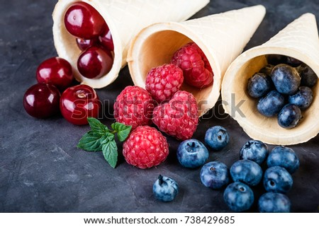 Waffle cones with fresh berries on a dark background close up