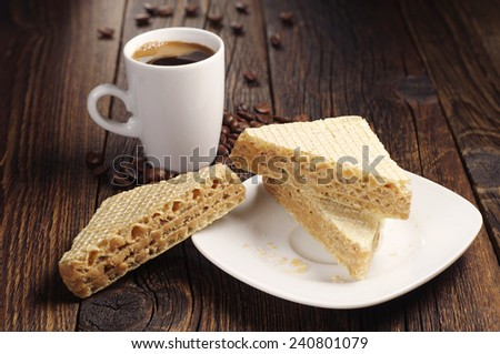 Waffle with caramelized condensed milk and cup of coffee on dark wooden table - stock photo