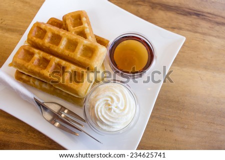 Waffle with maple syrup and fresh milk cream - stock photo