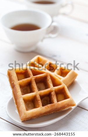 waffles and tea on white wooden board