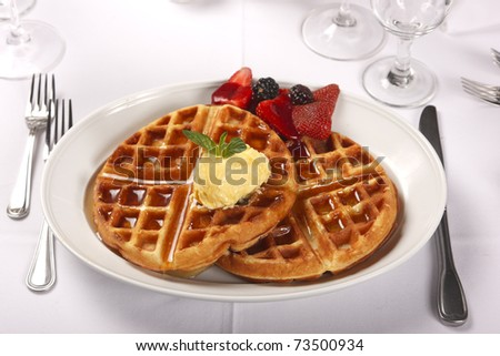Waffles served on a plate with fruit and melting butter - stock photo