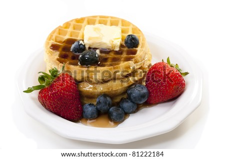 Waffles, strawberries, blueberries, and butter.   Isolated on white background. - stock photo