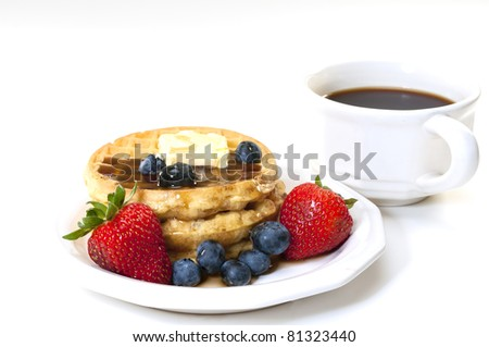 Waffles, strawberries, blueberries, and butter with cup of coffee.  Breakfast isolated on white background. - stock photo