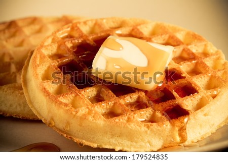 Waffles - This is a shot of a couple waffles with a slice of butter sitting on a plate getting covered with syrup. Shot with a shallow depth of field in a warm retro color tone. - stock photo